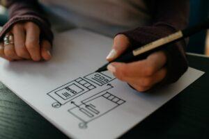 Person zeichnet Wireframes